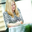 Blonde business woman standing and writing — Stock Photo #16217255