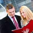 Stock Photo: Businessman and business woman talking over documents