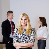 Portrait de femme d'affaires jeune avec son collègue à l'arrière — Photo