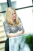 Blonde business woman standing and writing — Stock Photo