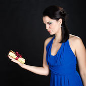 Beautiful woman showing a golden gift box — Stock Photo
