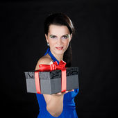 Beautiful woman presenting a gift box — Stock Photo
