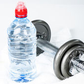 Grey dumbbell and water bottlle — Stock Photo