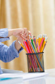Beautiful child choose between more colored pencil — Stock Photo