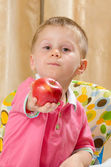 Beautiful child offering an apple — Stock Photo