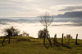 Field fence with a gate, with mountains in the background, and the fog in the valley, on a cold morning — Stock Photo