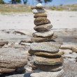 Tower made of pebbles of different sizes, stacked on the beach - Stock Photo
