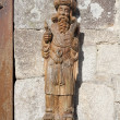 Figure of a saint carved in wood, hung on the facade of a building - Stock Photo