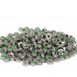 Heap of metal nuts with green interior, stacked, isolated on white - Stock Photo
