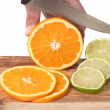 Hand cutting orange and lime slices on a wooden board, isolated en white — Stock Photo
