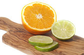 Orange and lime slices cut on a wooden board, isolated en white — Stock Photo