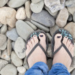 Girl feet in sandals, with blue nail polish on the beach rocks - Stock Photo