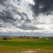 Stock Photo: Green fields and small village with cloudy sky