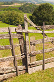 Rustic wooden barrier un a green field — Stock Photo