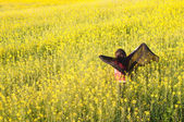 Girl holding a scarf in a rapeseed field — Stock Photo