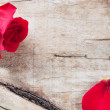 Red rose and petals on a wooden background — Stock Photo