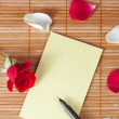 Pen and empty note on a wooden background with a rose and petals — Stok fotoğraf