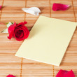 Blank note on a wooden background with a rose and petals — Stok fotoğraf