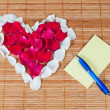 Heart made of rose petals, blank note and pen — Stock Photo