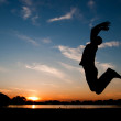 Silhouette of a man jumping in the sunset — Stock Photo