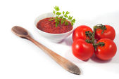 Tomato sauce on white bowl with some raw tomatoes isolated on white background — Stock Photo