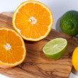 Limes, lemon, orange and tangerine on a wooden table, isolated on white — Stock fotografie