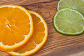 Orange and lime slices on a wooden table — Stockfoto