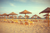 Empty deck loungers in the beach at sunset. Paradise in Algarve, Portugal — Stock Photo