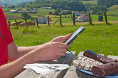 Man using a tablet while a breakfast outdoor, rural setting — Stock Photo