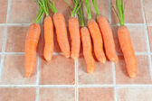 Bunch of carrots in the kitchen, on a tile background — Stock Photo