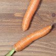 Bunch of carrots in kitchen, on wooden table background — Stock Photo #37292063