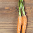 Bunch of carrots in kitchen, on wooden table background — Stock Photo #37292089