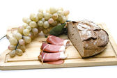 Plate of bread, ham and grapes — Stock Photo
