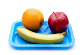 Red apple with bananas and orange on blue plate — Stock Photo