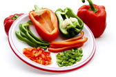 Red and green paprika in pieces and stripes on plate — Stock Photo
