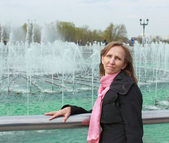 A woman stands near a fountain — Stock Photo