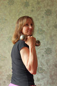 A woman with a dumbbell has been charging — Stock Photo