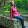 Stock Photo: Womsitting on stone bridge parapet