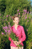A woman picking flowers willow-herb — Stock Photo