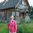 Stock Photo: Womstands near wooden house in village