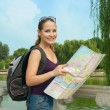 Young woman with backpack holding city map and having fun - Stock Photo