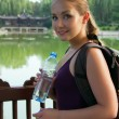 Portrait of young beautiful woman holding bottle of cold water — ストック写真