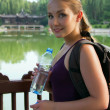 Portrait of young beautiful woman holding bottle of cold water — Stok fotoğraf