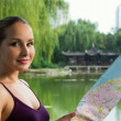Young tourist woman holding map. Student travel in China - Stock Photo