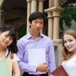 Group of American and Asian students  outside of college campus - 
