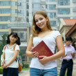 Young girl holding book and smiling. Group of studying students — Stok fotoğraf