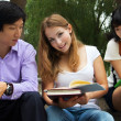 Group of American and Asian students  outside of college campus - Stock Photo