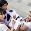 Teen girls and boy writing in books. Students studying together - Stock Photo