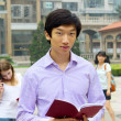 Portrait of young Asian man student carrying book  and smiling - Stock Photo