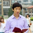 Portrait of young Asian man student carrying book and smiling — Stockfoto